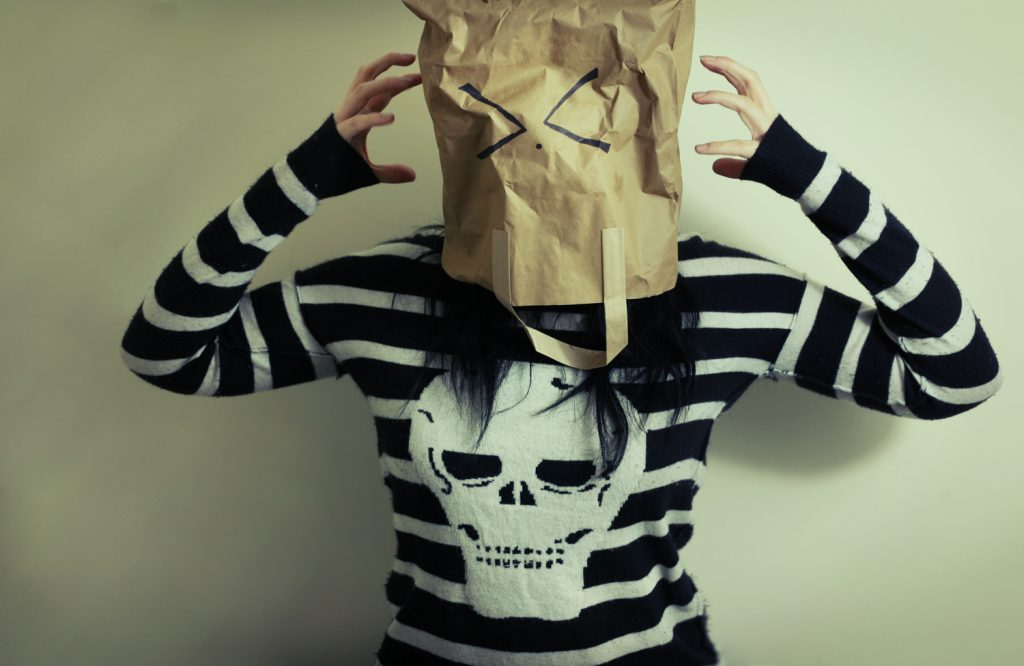Paper bag over head with frustrated face on it